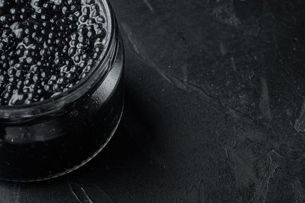 Glazen pot zwarte kaviaar, op zwarte tafel