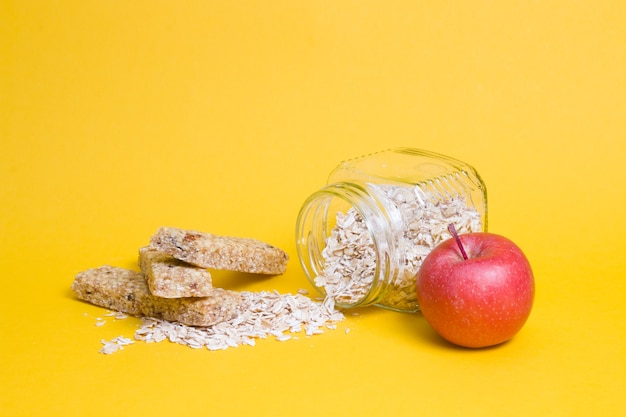Glazen potje met havermout, een appel en verschillende eiwitrepen voor een tussendoortje op een gele ondergrond