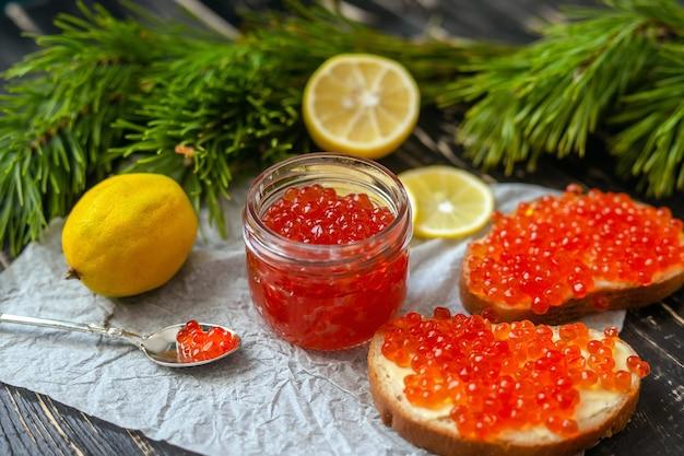 Glazen potje met rode kaviaar, citroenen en naalden op een zwarte houten tafel