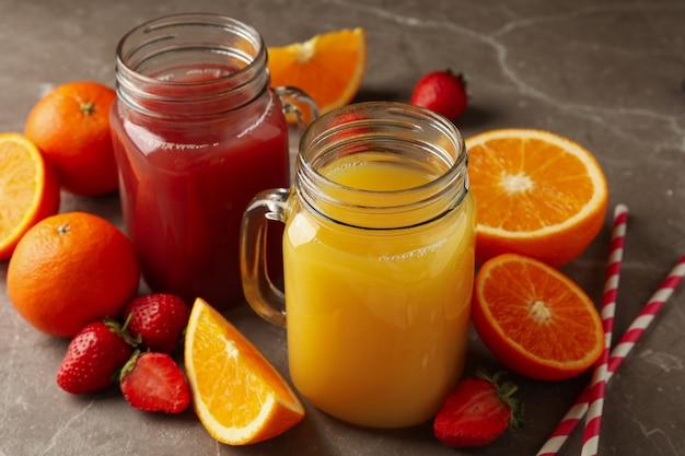 Glazen potten met aardbeien en sinaasappelsap op grijs