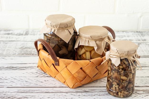 Glazen potten met ingeblikte champignons in een mand. gefermenteerd voedsel op een witte achtergrond met kopieerruimte.