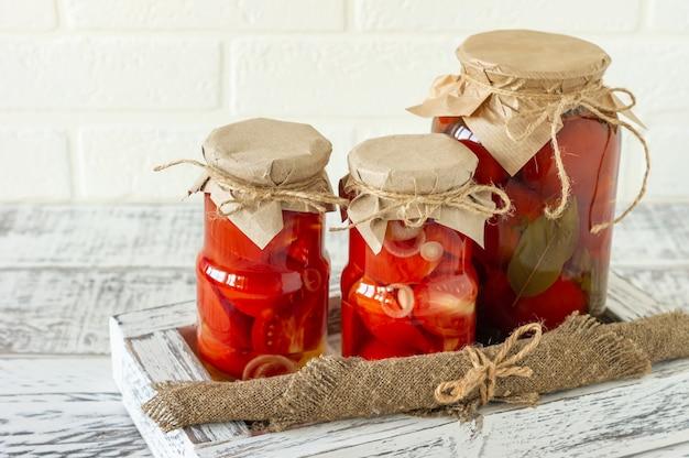 Glazen potten met ingeblikte tomaten met knoflook en peper. gefermenteerd voedsel op een witte houten achtergrond.