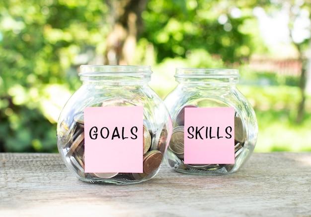 Glazen potten met munten en de inscripties goals en skills staan op een houten tafel. investeringsbudget.
