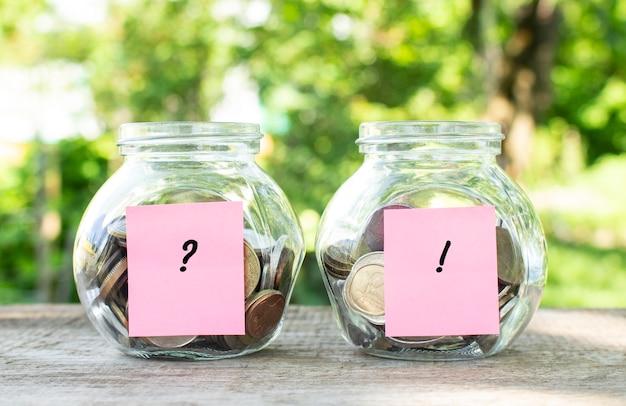 Glazen potten met munten en de inscripties staan op een houten tafel. investeringsbudget.