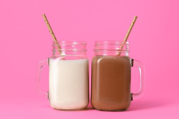 Glazen potten met op smaak gebrachte milkshakes tegen roze achtergrond