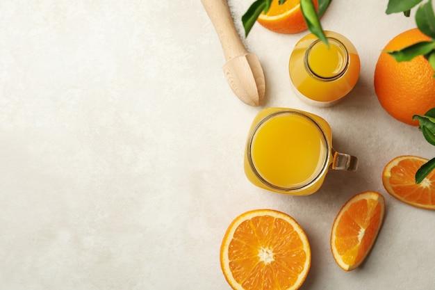 Glazen potten met sinaasappelsap op wit beige