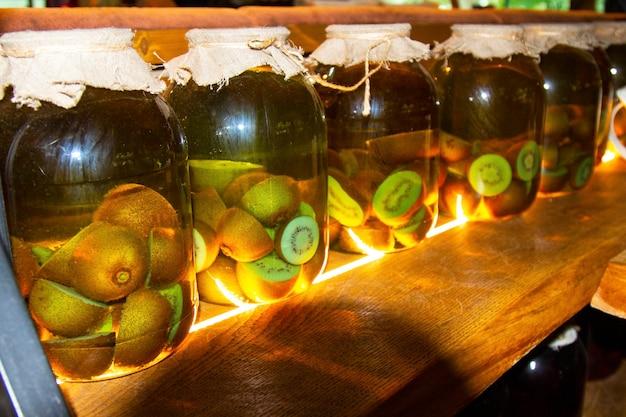 Glazen potten met spaties voor de winter. fruit- en bessenconserven in een donkere kelder. nuttige werkstukken