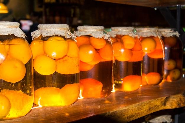 Glazen potten met spaties voor de winter. fruit- en bessenconserven in een donkere kelder. nuttige werkstukken Premium Foto