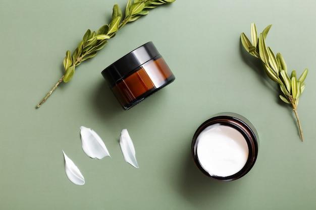 Glazen potten met vochtinbrengende crème en planten op groene achtergrond. concept van natuurlijke en moderne cosmetica