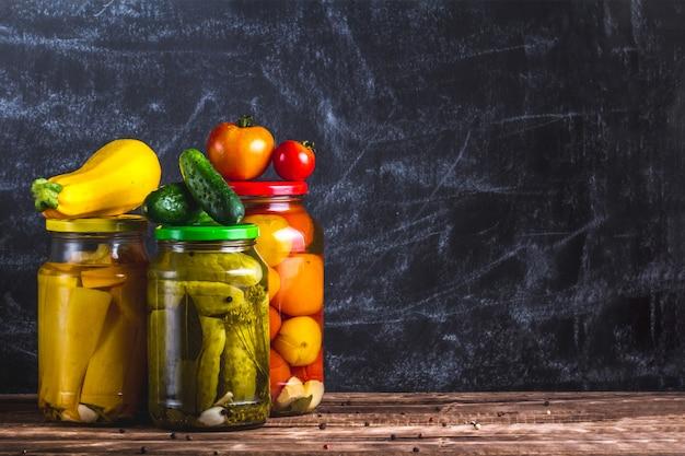 Glazen potten van ingemaakte, verse komkommers, courgettes en tomaten op een donkere achtergrond. kopieer ruimte. voorraad voedsel