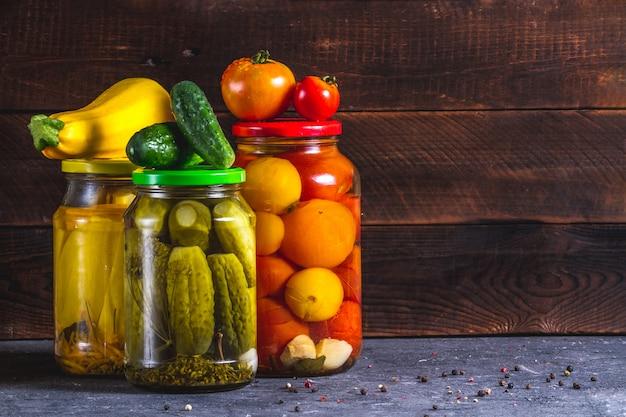 Glazen potten van ingemaakte, verse komkommers, courgettes en tomaten op een houten achtergrond. kopieer ruimte.