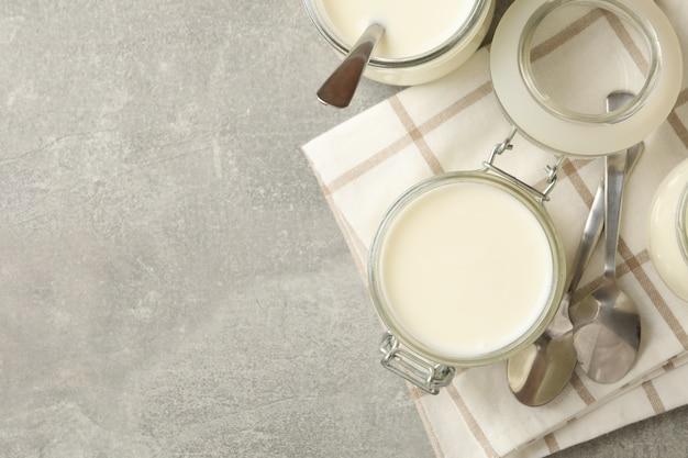 Glazen potten yoghurt, lepels en servet op grijze achtergrond