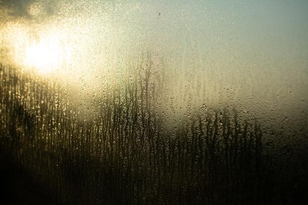 Glazen raam reflecterend licht door zijn natte textuur