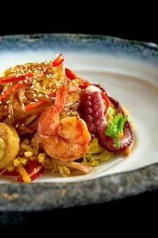 Glazen rijstnoedels in zoetzure saus met garnalen, coquilles, octopus en inktvis, geserveerd in een witte kom