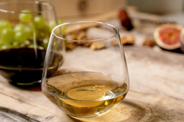 Glazen rode en witte wijn met druiven, vijgen, geitenkaas en walnoten over oude houten achtergrond. detailopname