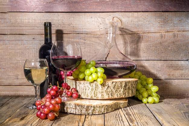 Glazen rode en witte wijn met zonneschijn en schaduwen, met fles en karaf, tros druiven, op houten ondergrond met biologische sokkels, herfstoogst, wijnmakerijconcept