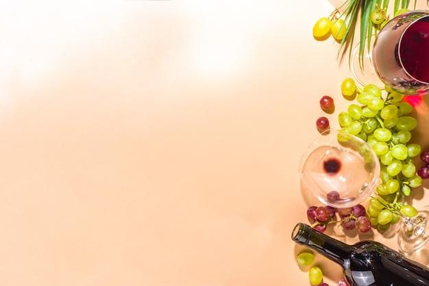 Glazen rode en witte wijn met zonneschijn en schaduwen, met fles en karaf, tros druiven, op romige kleurachtergrond, flatlay bovenaanzicht wijnproeverij, herfstoogst, wijnmakerijconcept