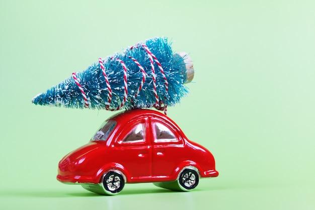 Glazen rode speelgoedauto met kerstversiering op groen
