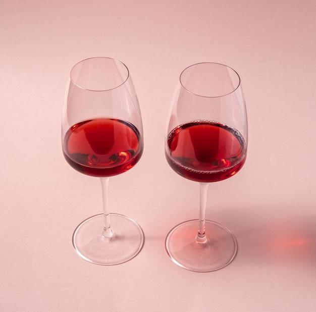 Glazen rode wijn op roze tafel, bovenaanzicht.