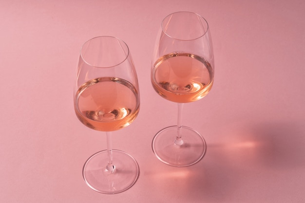 Glazen rose wijn op roze tafel, bovenaanzicht.