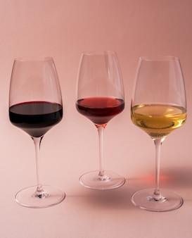 Glazen roze, witte en rode wijn op roze achtergrond, vooraanzicht.