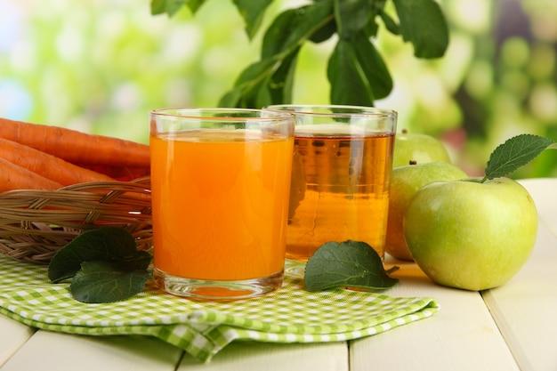 Glazen sap, appels en wortelen op witte houten tafel
