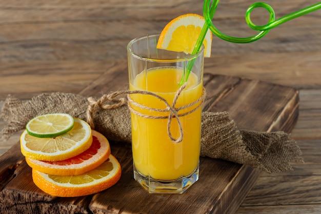 Glazen sap en citrusvruchten op een houten tafel. rustieke stijl.