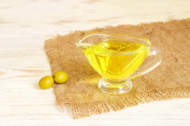 Glazen sausboot met extra vergine olijfolie en verse groene olijven op jute doek op houten tafel.