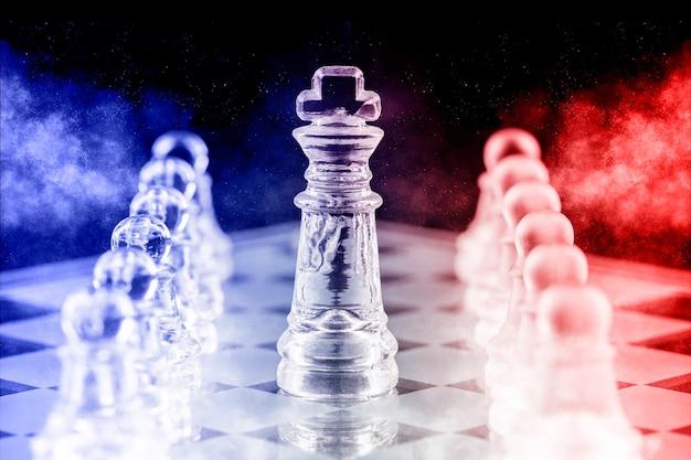 Glazen schaakstukken met blauw en rood licht op een glazen schaakbord met reflectie, op een zwarte achtergrond.