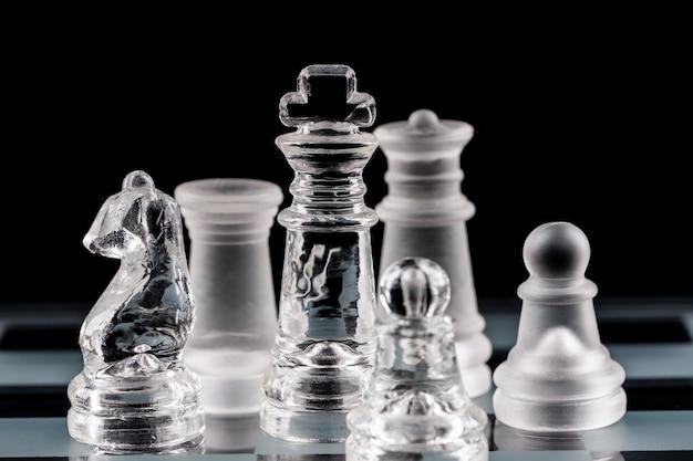 Glazen schaakstukken op een glazen schaakbord met reflectie, op een zwarte achtergrond.
