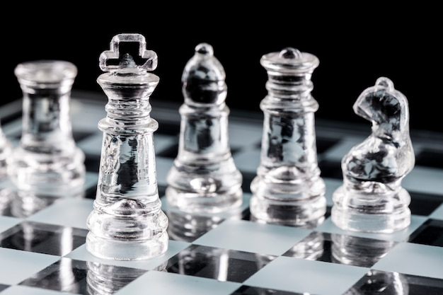 Glazen schaakstukken op een glazen schaakbord met reflectie.