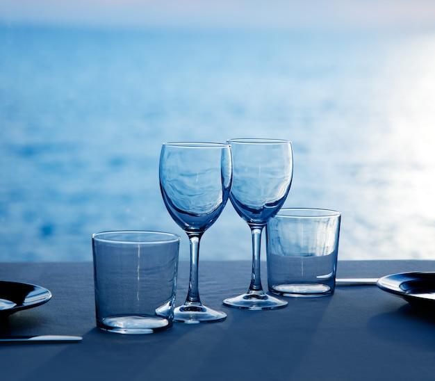 Glazen schaal kopjes en glazen op blauwe zee