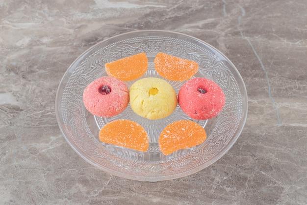 Glazen schaal met koekjes en gelei-snoepjes op marmeren oppervlak