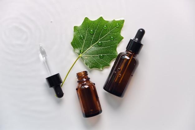 Glazen serum cosmetische bruine fles met pipet op water achtergrond. mooie vlekken op het water met groen blad. mockup van cosmetische producten