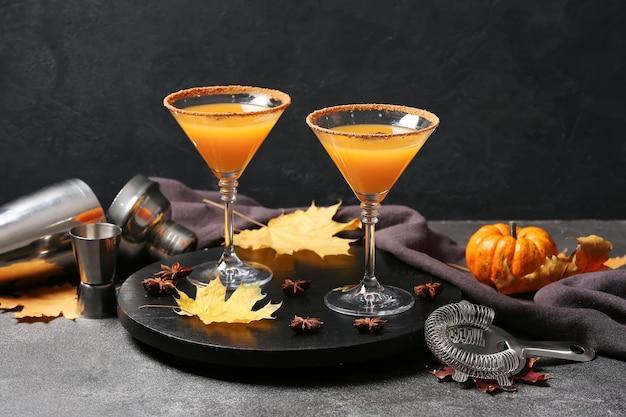 Glazen smakelijke pompoentaart martini op donkere tafel