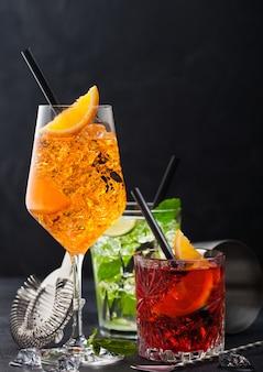 Glazen spritz, mojito en negroni-cocktails met ijsblokjes en limoen- en sinaasappelschijfjes met muntblad en zwart stro op donkere achtergrond met zeef en lepel.