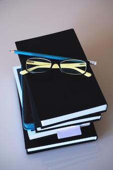 Glazen staan op een stapel boeken, naast een potlood.