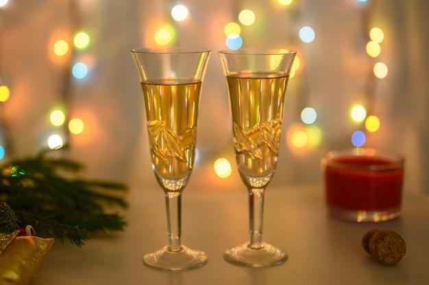 Glazen tegen de achtergrond van een lichtgevende slinger zijn voorbereid op het nieuwe jaar.