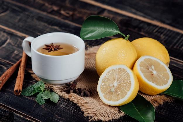 Glazen thee met citroen, gesneden citroenen op een snijplank