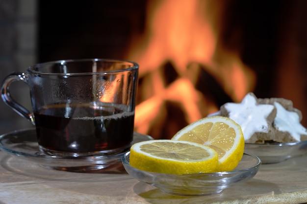 Glazen theekop en citroen, voor gezellige open haard, in landhuis, wintervakantie.