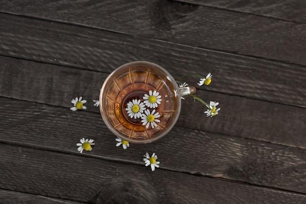 Glazen theekop met kamille op een houten oppervlak.