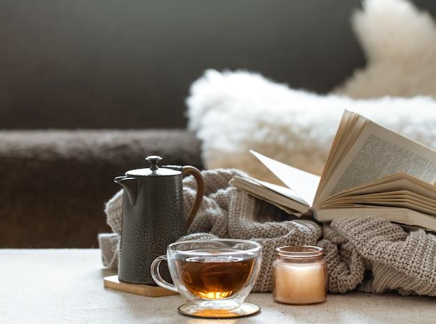 Glazen theekop, theepot en boek met gebreid element op onscherpe achtergrond. het concept van wooncomfort en warmte.