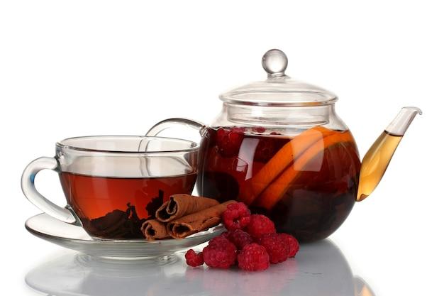 Glazen theepot en kopje met zwarte thee van frambozen, sinaasappel, limoen geïsoleerd op wit