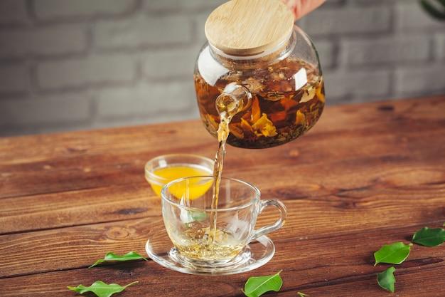 Glazen theepot met kopje zwarte thee op houten tafel