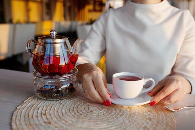 Glazen theepot met thee in café. vrouwenhanden met theekop op achtergrond