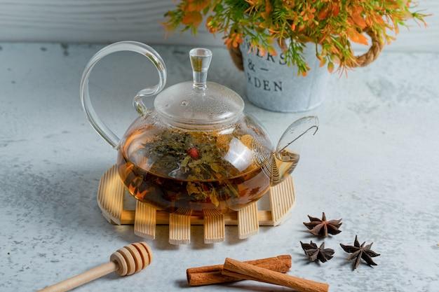 Glazen theepot vol met vers gezette thee op grijze muur.