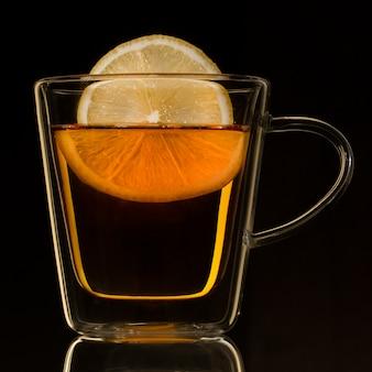 Glazen transparante beker met thee en citroen op een zwarte achtergrond.
