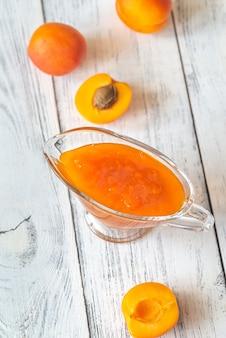 Glazen vaas met abrikozenjam met verse abrikozen op hout