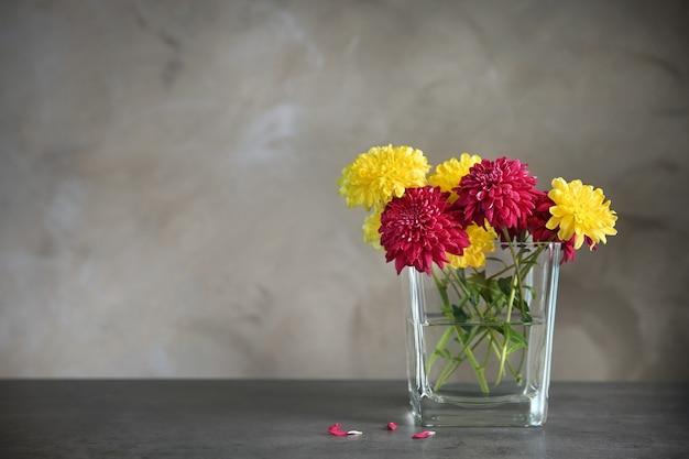 Glazen vaas met boeket mooie bloemen op kleur