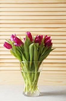 Glazen vaas met boeket van mooie tulpen op houten achtergrond